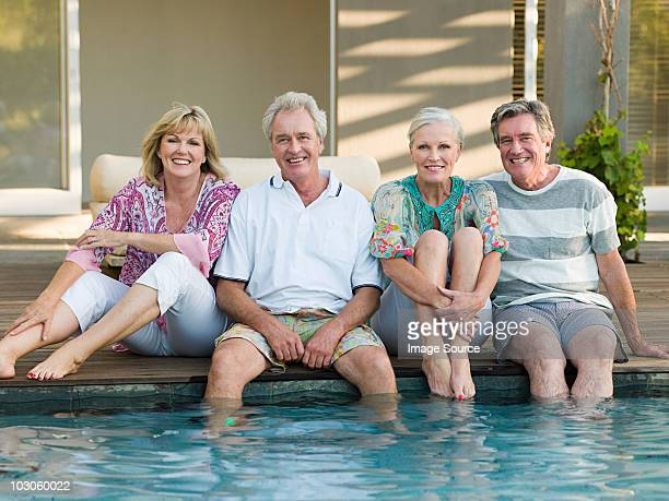 mature friends by swimming pool - 50 59 jaar stockfoto's en -beelden