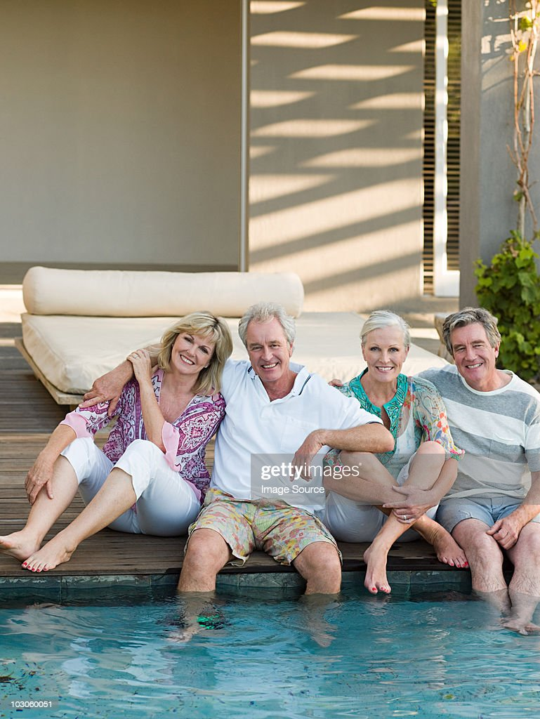 Mature friends by swimming pool : Stock Photo