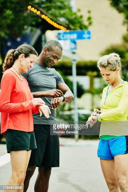 Mature friends checking smart watches before morning run