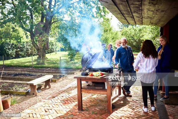 mature friends cooking on barbecue in vegetable garden - garden stock pictures, royalty-free photos & images