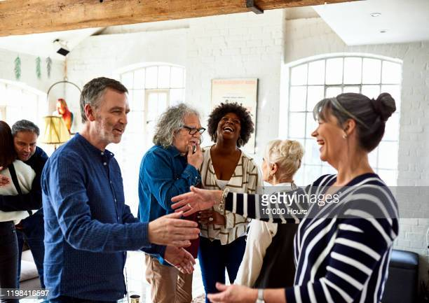 mature friends greeting each other at social gathering - multi ethnic group stock pictures, royalty-free photos & images