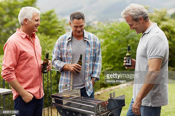 mature friends having beer while barbecuing - only mature men stock pictures, royalty-free photos & images