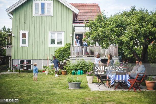 mature friends having garden party while children playing in backyard during summer weekend - barbecue social gathering stock pictures, royalty-free photos & images
