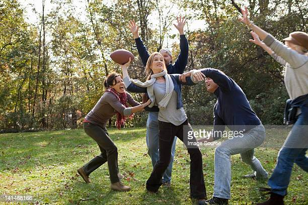Mature friends playing football