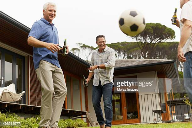 mature friends playing soccer at yard - nur erwachsene stock-fotos und bilder