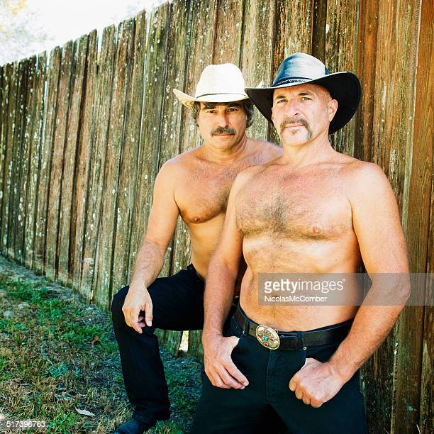 mature gay bear hairy couple shirtless portrait with fence - hairy chest stockfoto's en -beelden