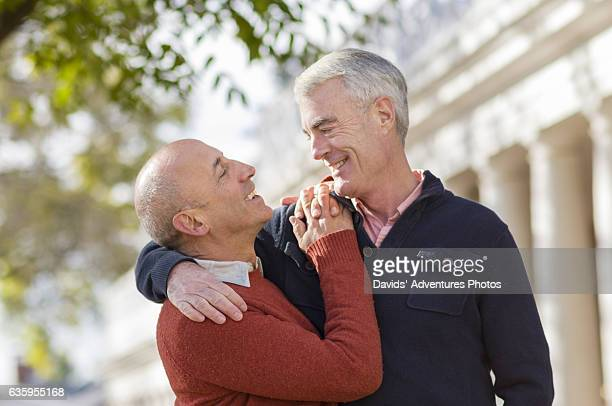 mature gay couple affectionately embracing and smiling at each other in front of building with columns - alumni stock pictures, royalty-free photos & images