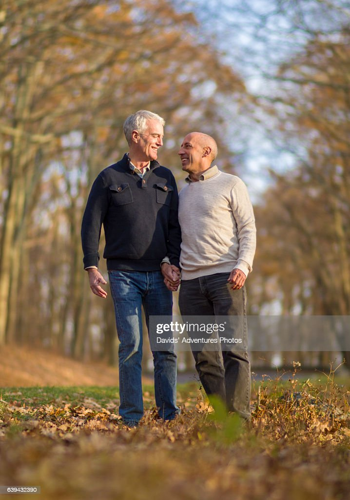 Mature Gay Couple Affectionately Holding Hands While Walking Or Hiking On Country Road -1506
