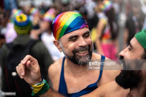 mature gay couple dansant sur la gay pride parade - gay seniors photos et images de collection