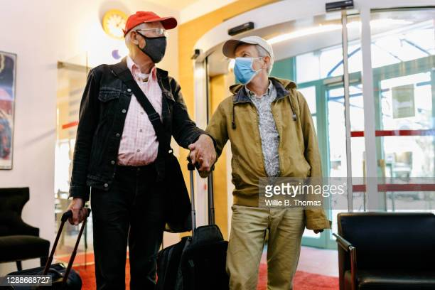 mature gay couple holding hands while entering hotel together - hotel stock pictures, royalty-free photos & images