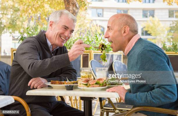 mature gay couple sitting in outdoor urban restaurant while one affectionately lets the other taste his meal - gay seniors photos et images de collection