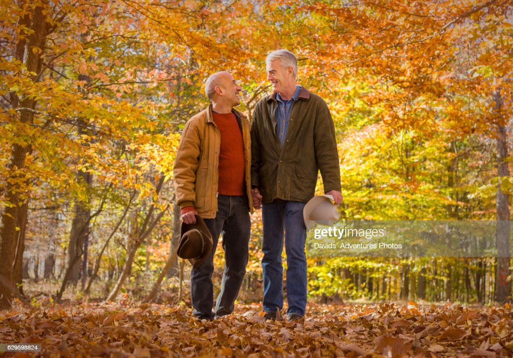 Mature Gay Cowboys Holding Hands While Walking Through Colorful Woods In Autumn Stock -5291