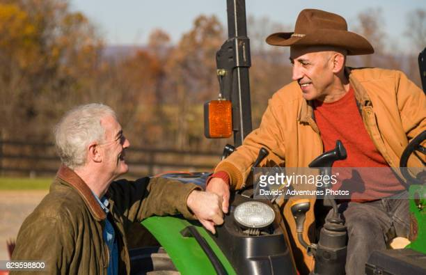 Mature Gay Cowboys or Ranchers Affectionately Holding Hands While One is on Tractor
