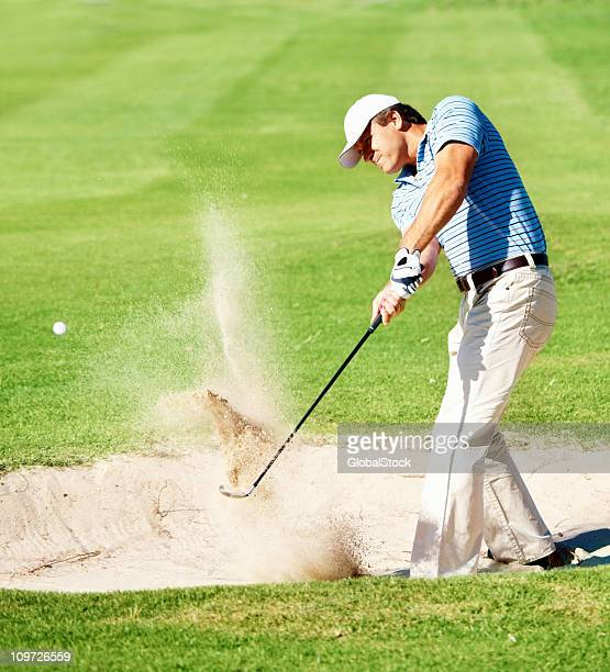 Mature golfer chipping the ball from sand trap