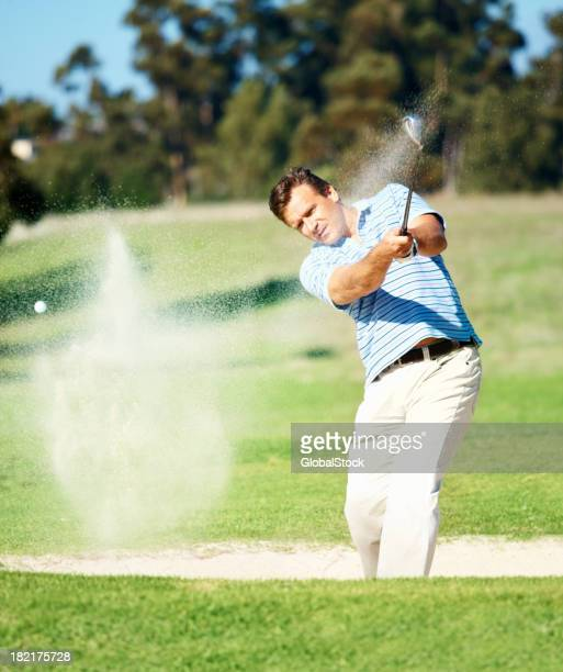 mature golfer hitting out of a sand trap - golf swing stock pictures, royalty-free photos & images