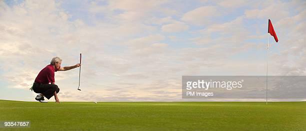 Mature golfer lining up a putt
