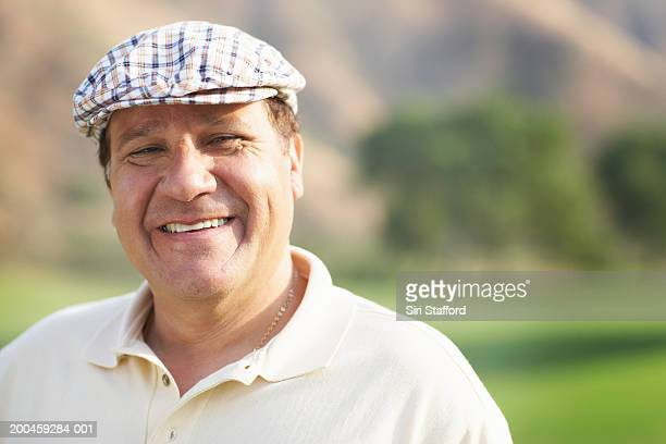 mature golfer standing on course, smiling - flat cap stock photos and pictures
