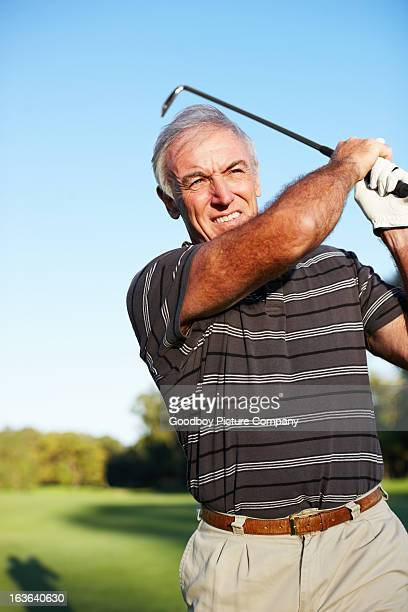 Mature golfer swinging