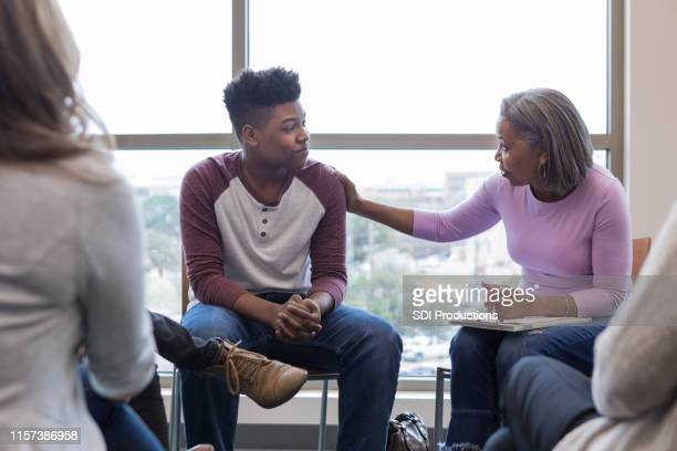 mature grandmother lays hand on teen grandson to reassure him - adolescence stock pictures, royalty-free photos & images