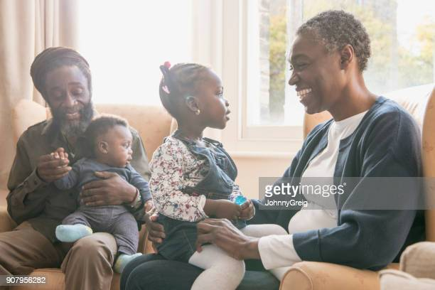 mature grandparents at home looking after grandchildren - afro caribbean ethnicity stock pictures, royalty-free photos & images
