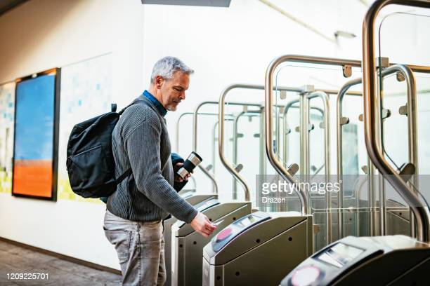 mature gray hair man commuting and using contactless payment to purchase ticket - netherlands stock pictures, royalty-free photos & images