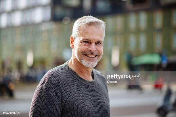 rijpe grijze haarmens die camera bekijkt en glimlacht - alleen mannen stockfoto's en -beelden