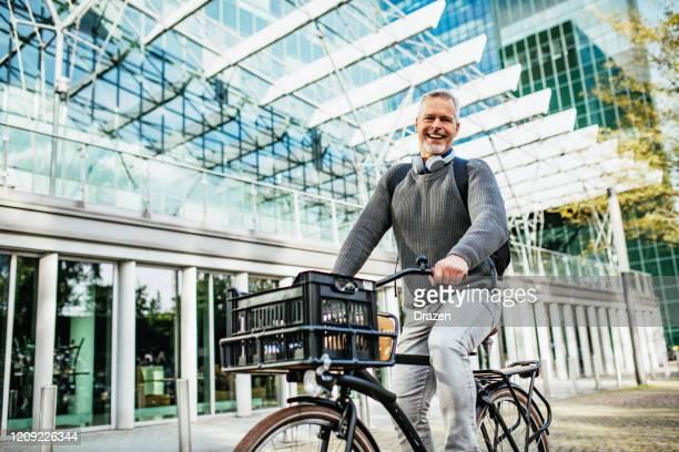 volwassen grijs haar man fietsen en draagt bij aan eco-vriendelijke omgeving - nederlandse cultuur stockfoto's en -beelden