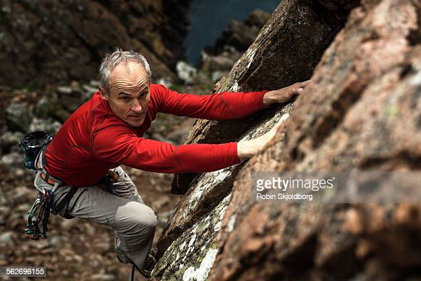 Mature grey haired Man climbing up cliff