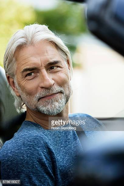 Mature grey haired Man in open car