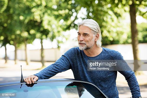 mature grey haired man leaning on open car - handsome 50 year old men stock photos and pictures