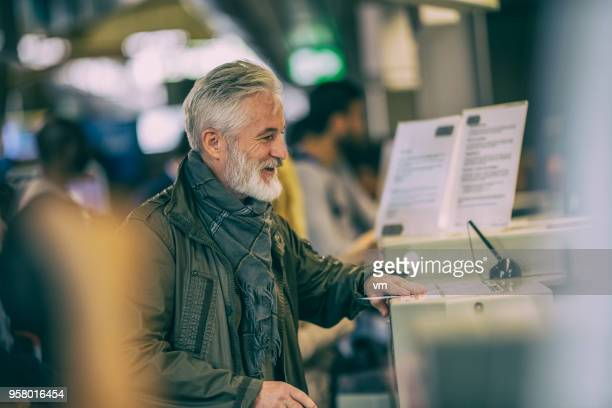 Mature grey-haired man checking in at airport counter