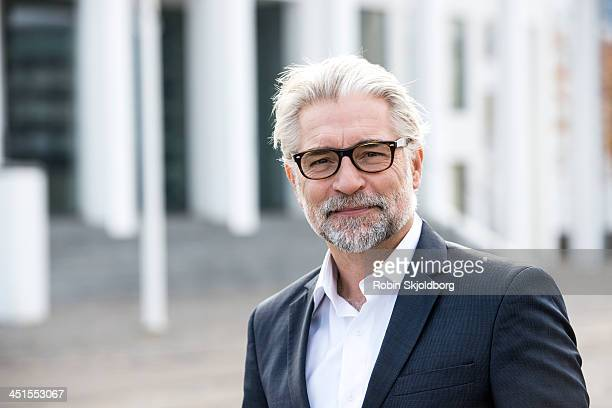 mature grey-haired man in suit - focus on foreground stock pictures, royalty-free photos & images