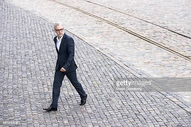 Mature grey-haired man in suit walking