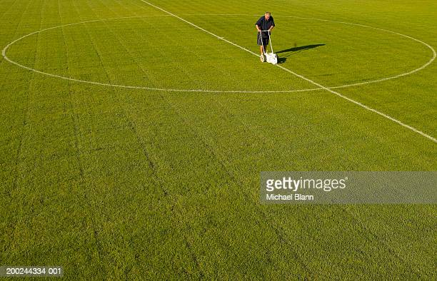 Mature groundsman marking lines on football pitch, elevated view