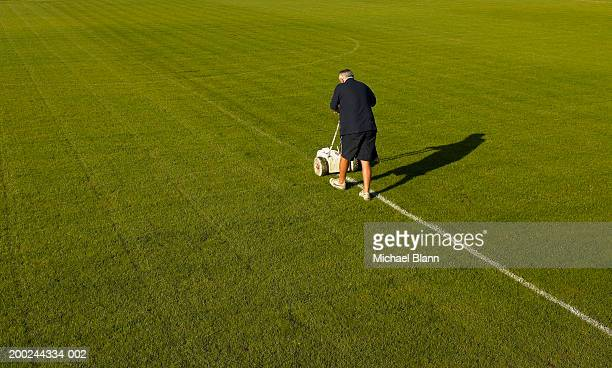 Mature groundsman marking lines on football pitch, rear view