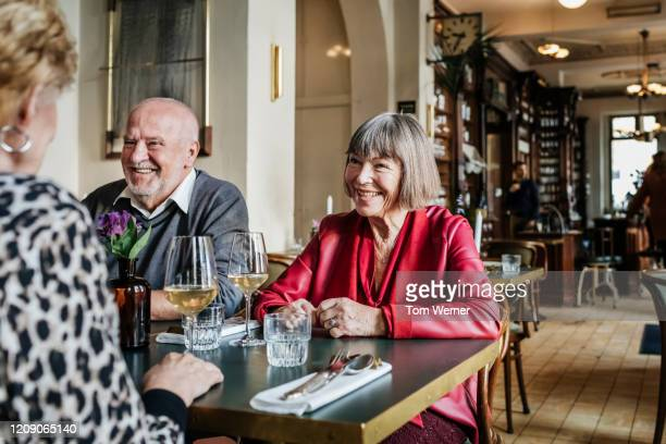mature group of friends sitting in restaurant together - kleine personengruppe stock-fotos und bilder