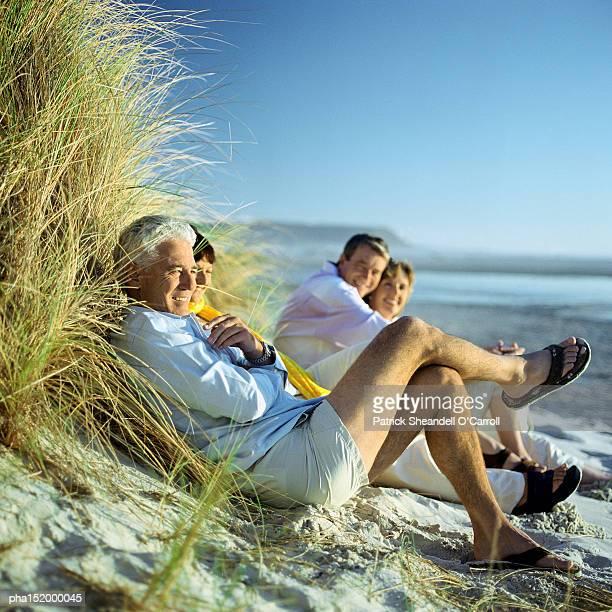 Mature group sitting on beach.