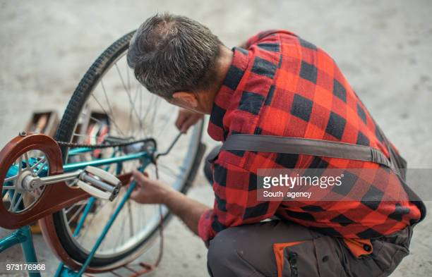 Mature guy fixing bicycle