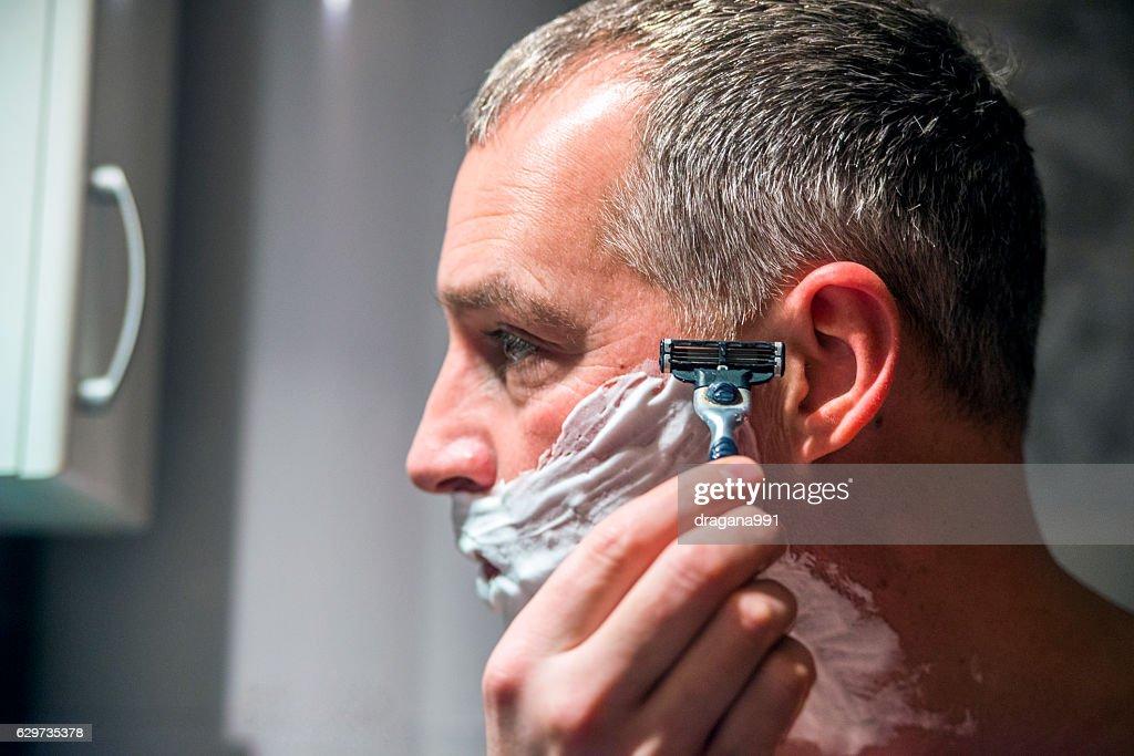 Mature Handsome man shaving his beard in bathroom. : Stock Photo
