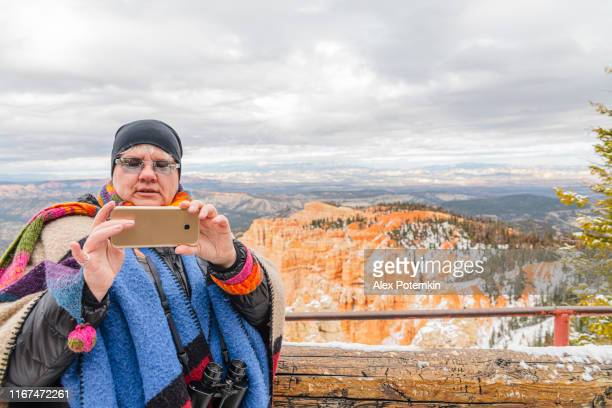 mature happy, body-positive, 45-years-old caucasian woman enjoying bryce canyon national park and take selfies at rainbow point overlook. utah, usa, in the late fall. - 45 49 anni foto e immagini stock