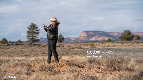 mature happy, body-positive, 45-years-old caucasian woman enjoying the nature in a highland valley in utah, nearby bryce canyon. ефлштп pictures with a smartphone. - 45 49 anni foto e immagini stock