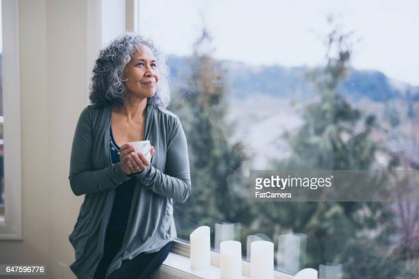 Oudere Hawaiiaanse vrouw het drinken van thee in de ochtend door raam
