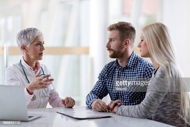 Reife medizinische Arbeiter der Kommunikation mit junges Paar in Arzt-Büro.
