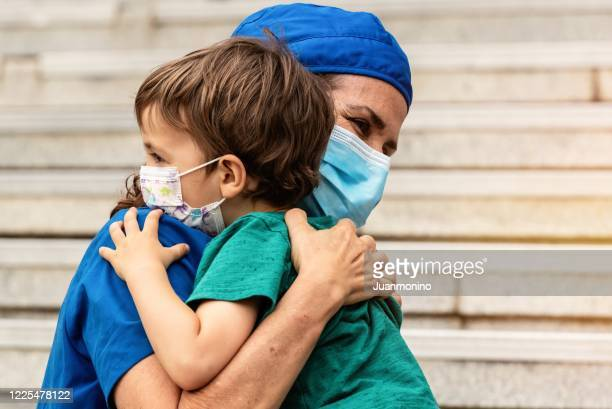 mature healthcare worker posing hugging her son after coming back from the hospital to fight contagion pandemic - child hospital stock pictures, royalty-free photos & images