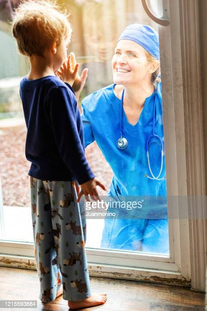 mature healthcare worker posing seeing her son with a window glass separating them to avoid possible contagion - vertical stock pictures, royalty-free photos & images