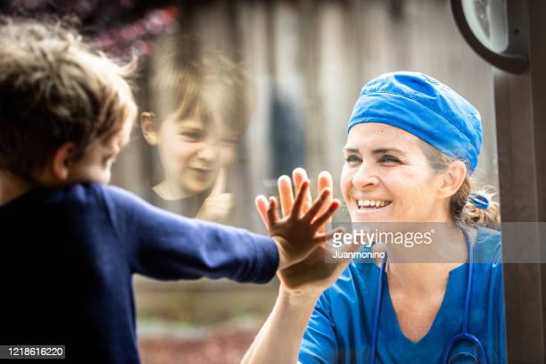mature healthcare worker posing seeing her son with a window glass separating them to avoid possible contagion - affectionate stock pictures, royalty-free photos & images