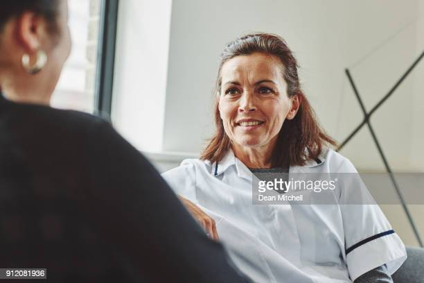 mature healthcare worker talking with female patient - nursing assistant stock pictures, royalty-free photos & images