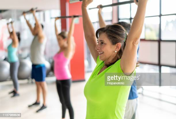 mature healthy woman working out at the gym during class smiling - hispanolistic stock photos and pictures