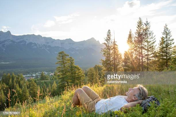 mature hiker reclines in mountain meadow at sunset - one mature man only stock pictures, royalty-free photos & images