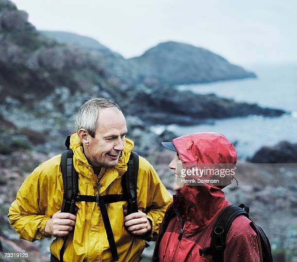 Mature hikers on nature trail in rain
